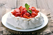 Cake pavlova with strawberry on wooden table