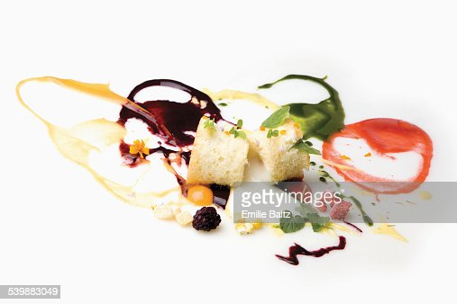 Cake slices garnished with spilled sauces and berries against white background