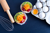 cakes, eggs in a tray with a rolling pin and a whisk on the table whith dark background