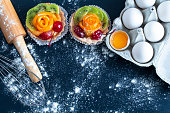 cakes, eggs in a tray with a rolling pin and a whisk on the table with flour, on a black background