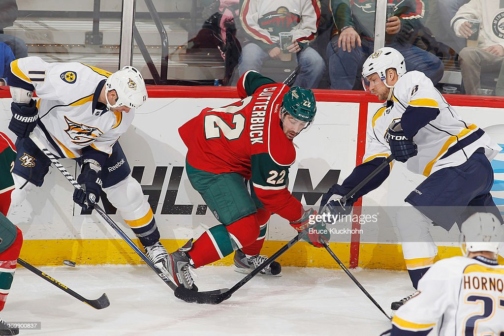 Cal Clutterbuck #22 of the Minnesota Wild battles for control of the puck with (L-R) David Legwand #11 and Kevin Klein #8 of the Nashville Predators during the game on January 22, 2013 at the Xcel Energy Center in Saint Paul, Minnesota.
