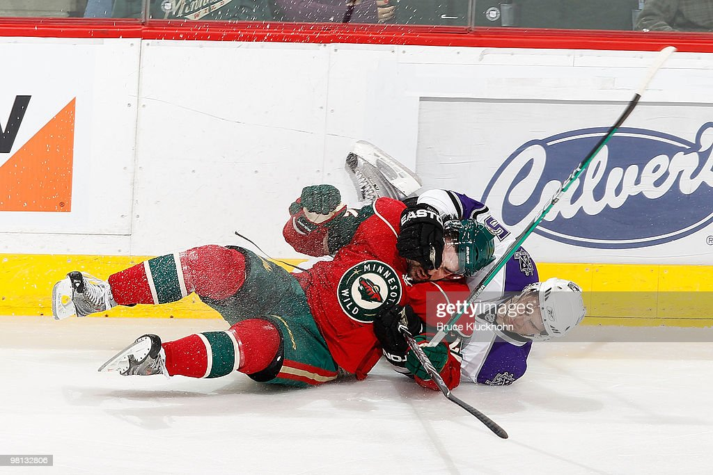 Cal Clutterbuck of the Minnesota Wild is taken down by Peter Harrold of the Los Angeles Kings during the game at the Xcel Energy Center on March 29...