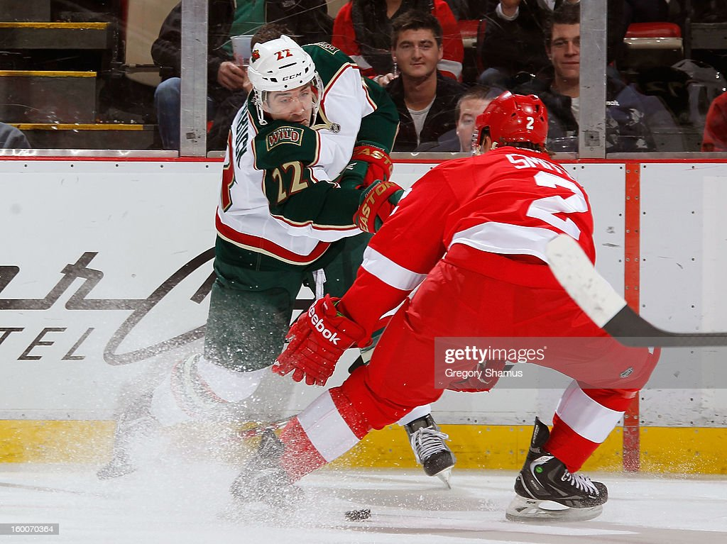 Cal Clutterbuck #22 of the Minnesota Wild tries to get a first period shot through the defense of Brendan Smith #2 of the Detroit Red Wings at Joe Louis Arena on January 25, 2013 in Detroit, Michigan.