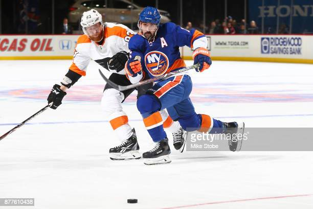 Cal Clutterbuck of the New York Islanders and Jakub Voracek of the Philadelphia Flyers chase down a loose puck during the second period of a game at...