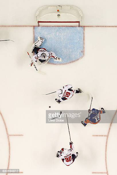 Cal Clutterbuck of the New York Islanders battles for the puck against Marcus Johansson and Nicklas Backstrom of the Washington Capitals at the...