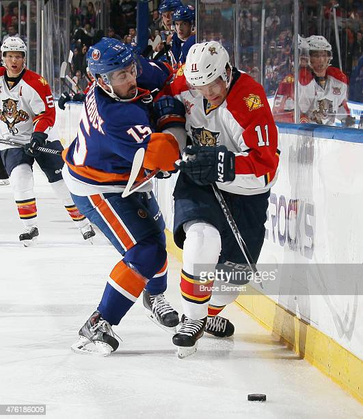Cal Clutterbuck of the New York Islanders checks Jonathan Huberdeau of the Florida Panthers along the boards during the third period at the Nassau...