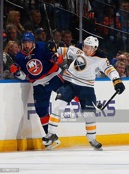 Cal Clutterbuck of the New York Islanders gets checked into the boards by Brian Flynn of the Buffalo Sabres at Nassau Veterans Memorial Coliseum on...