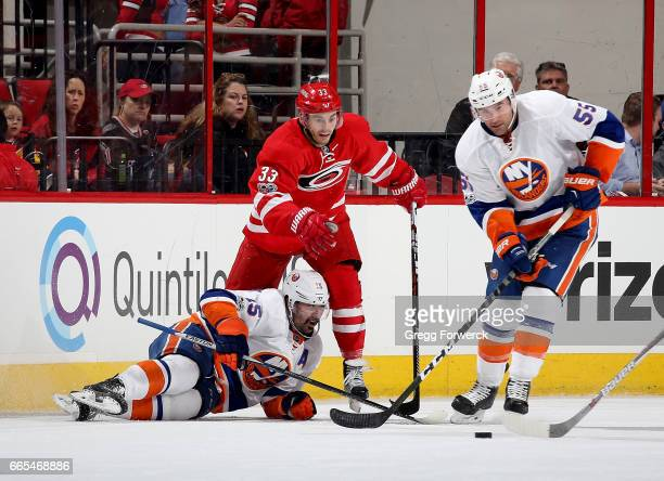 Cal Clutterbuck of the New York Islanders goes down on the ice as he battles with Derek Ryan of the Carolina Hurricanes for the loose puck and...