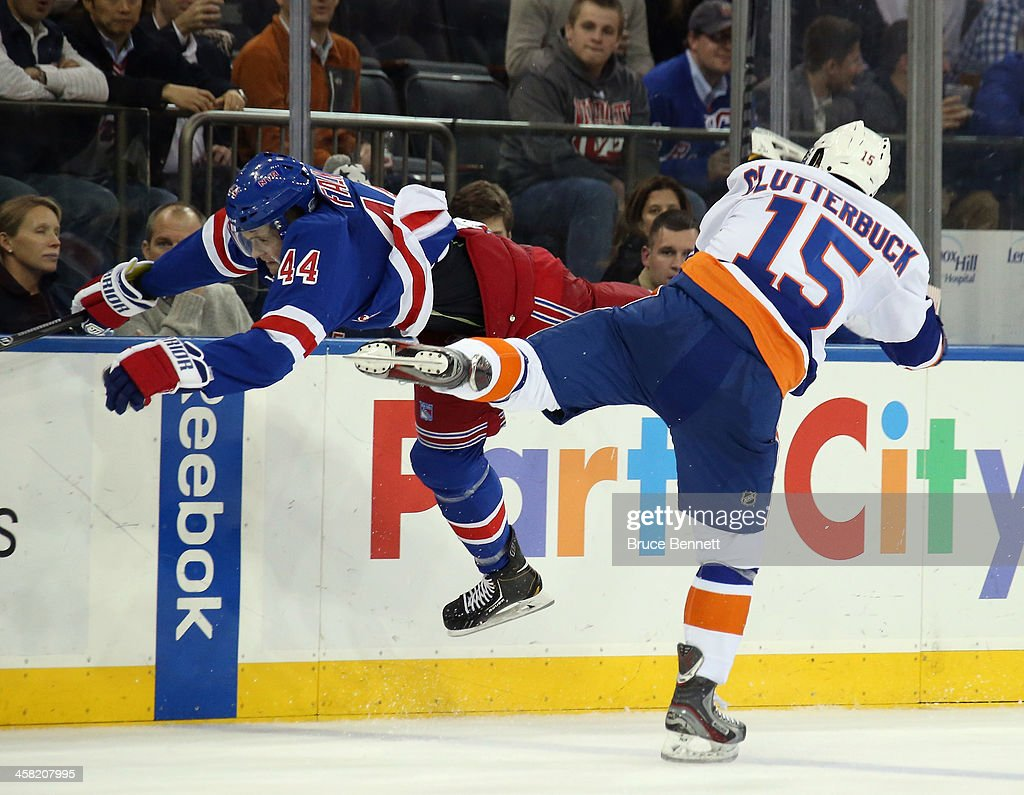 <a gi-track='captionPersonalityLinkClicked' href=/galleries/search?phrase=Cal+Clutterbuck&family=editorial&specificpeople=570497 ng-click='$event.stopPropagation()'>Cal Clutterbuck</a> #15 of the New York Islanders hits <a gi-track='captionPersonalityLinkClicked' href=/galleries/search?phrase=Justin+Falk&family=editorial&specificpeople=4324950 ng-click='$event.stopPropagation()'>Justin Falk</a> #44 of the New York Rangers during the third period at Madison Square Garden on December 20, 2013 in New York City. The Islanders defeated the Rangers 5-3.