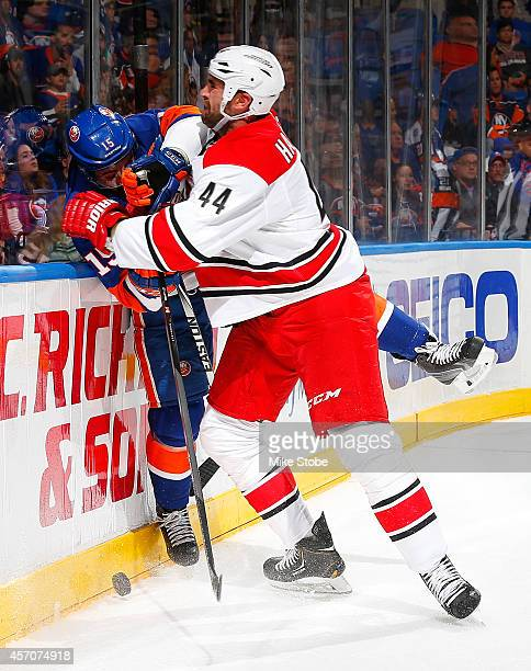 Cal Clutterbuck of the New York Islanders is checked into the boards by Jay Harrison of the Carolina Hurricanes at Nassau Veterans Memorial Coliseum...