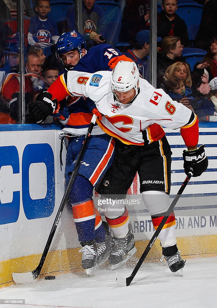 Cal Clutterbuck #15 of the New York Islanders is held off by Dennis Wideman #6 of the Calgary Flames at Nassau Veterans Memorial Coliseum on February 6, 2014 in Uniondale, New York.