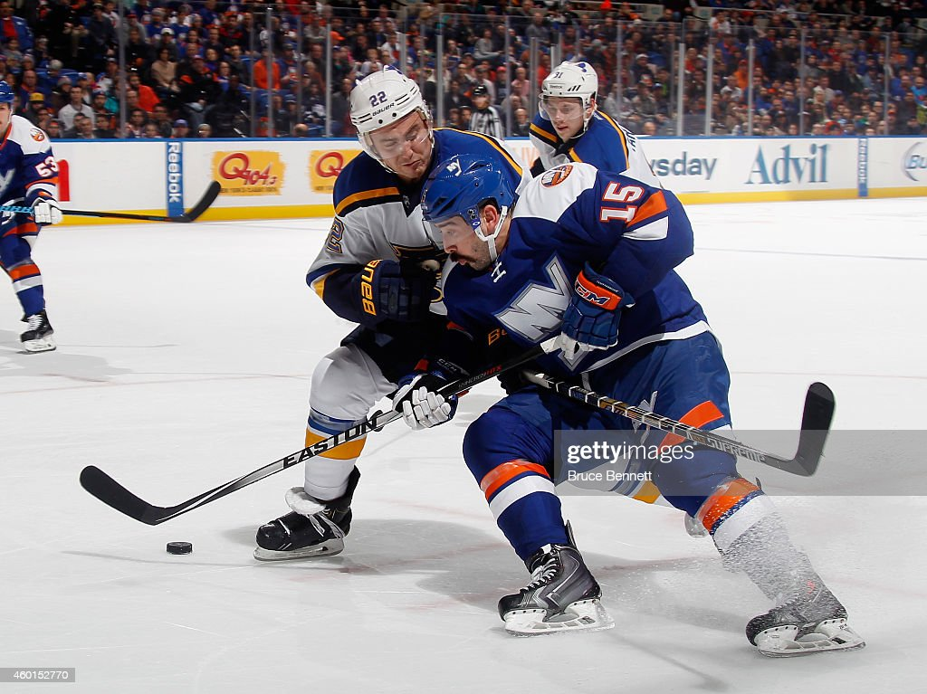Cal Clutterbuck of the New York Islanders is held up Kevin Shattenkirk of the St Louis Blues at the Nassau Veterans Memorial Coliseum on December 6...