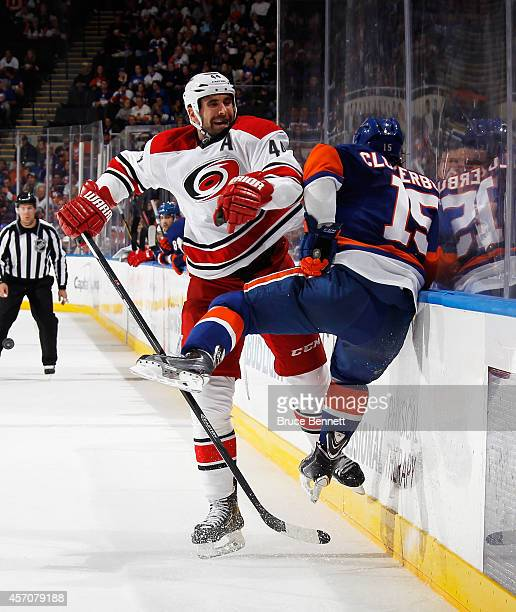 Cal Clutterbuck of the New York Islanders is hit by Jay Harrison of the Carolina Hurricanes during the third period at the Nassau Veterans Memorial...