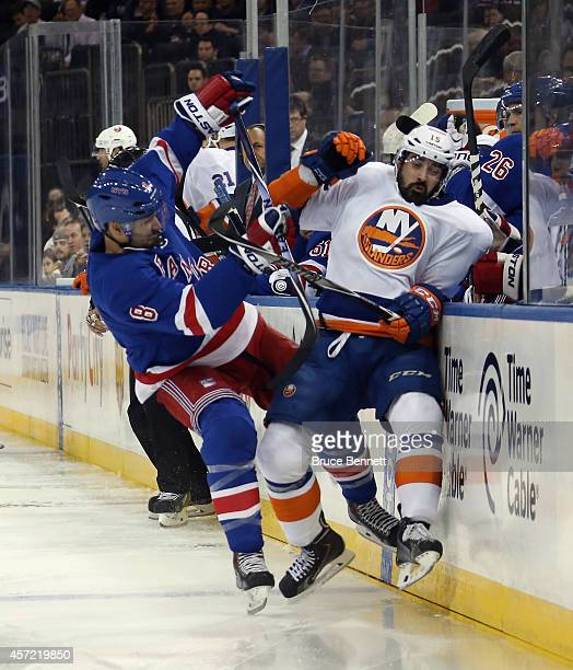Cal Clutterbuck of the New York Islanders is unpended by Kevin Klein of the New York Rangers during the first period at Madison Square Garden on...