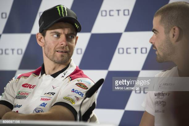 Cal Crutchlow of Great Britain and LCR Honda speaks with Romano Fenati of Italy and Marinelli Rivacold Snipers Team during the press conference at...