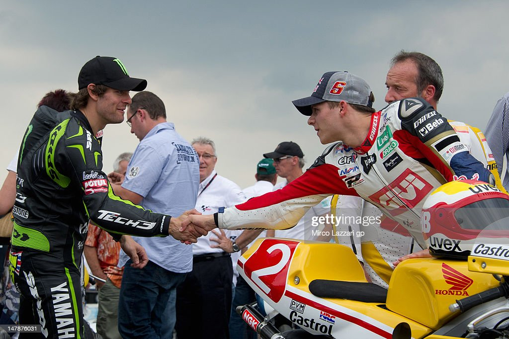 Cal Crutchlow of Great Britain and Monster Yamaha Tech 3 greets Stefan Bradl of Germany and LCR Honda MotoGP on the grid during the pre-event 'MotoGP riders celebrate Sachsenring's 85th Anniversary' during the MotoGp of Germany at Sachsenring Circuit on July 5, 2012 in Hohenstein-Ernstthal, Germany.