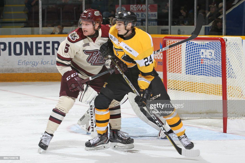 Cal Davis #24 of the Kingston Frontenacs battles against Alex Black #5 of the Peterborough Petes in an OHL game at the Peterborough Memorial Centre on October 12, 2017 in Peterborough, Ontario.