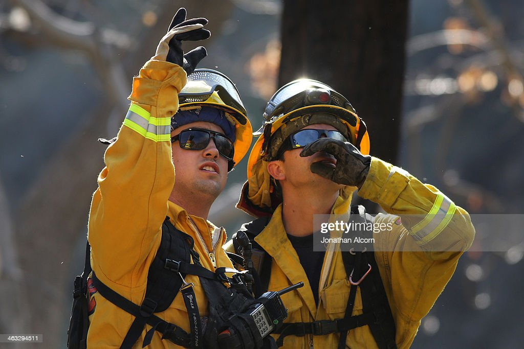 A Cal Fire crew work at a flare-up at the Colby Fire burning for a second day in the hillside above Highway 39 on January 17, 2014 in Azusa, California. The so-called Colby Fire, has burned about 1,700 acres in the Angeles National Forest north of Glendora and Azusa.