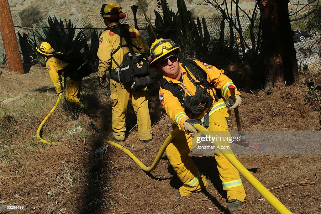 A Cal Fire crew work on a flare-up at the Colby Fire burning for a second day in the hillside above Highway 39 on January 17, 2014 in Azusa, California. The so-called Colby Fire, has burned about 1,700 acres in the Angeles National Forest north of Glendora and Azusa.
