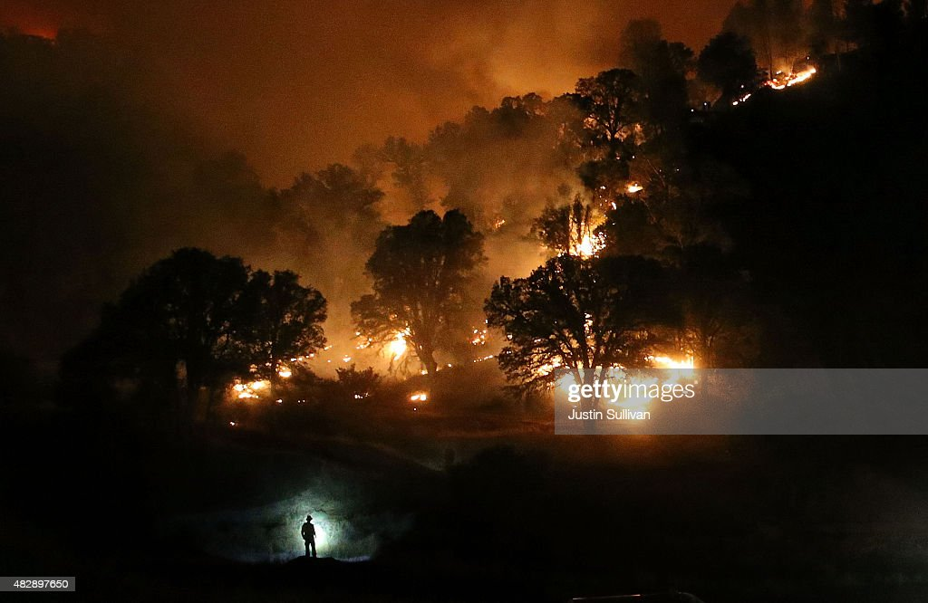 Cal Fire firefighter is silhouetted by his headlamp as he monitors a backfire while battling the Rocky Fire on August 3 2015 near Clearlake...