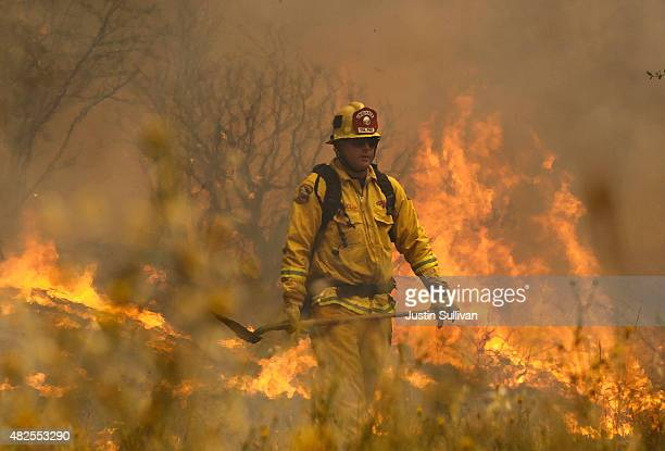 Cal Fire firefighter Johnny Miller monitors flames from the Rocky Fire as it approaches a home on July 31 2015 in Lower Lake California Over 900...