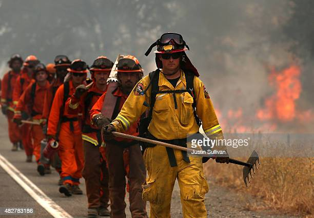 Cal Fire firefighter leads a group of inmate firefighters during a burn operation to head off the Rocky Fire on August 2 2015 near Clearlake...