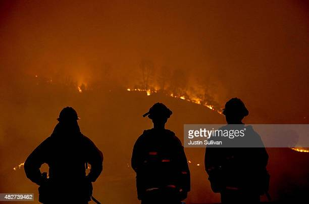 Cal Fire firefighters look on as the Rocky Fire burns through trees on August 2 2015 near Clearlake California Over 1900 firefighters are battling...