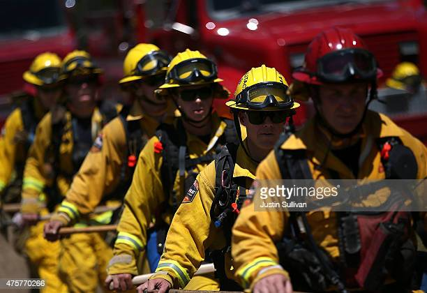3 Cal Fire firefighters march through a field of dry grass during a live fire training on June 3 2015 in Mt Hamilton California Cal Fire firefighters...