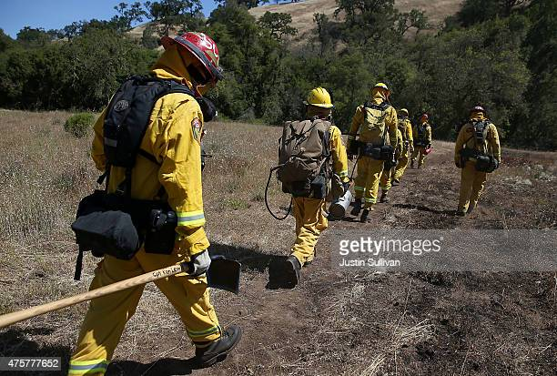 Cal Fire firefighters march through a field of dry grass during a live fire training on June 3 2015 in Mt Hamilton California Cal Fire firefighters...