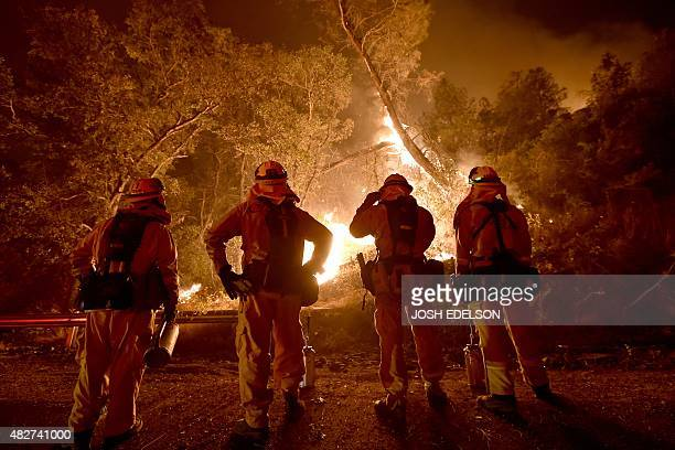 Cal Fire firefighters watch a back burn while fighting the Rocky fire off highway 20 near Clear Lake California on August 2 2015 The fire has charred...