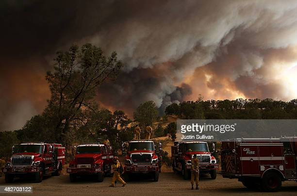 Cal Fire firefighters watch a large plume of smoke as it rises from the Rocky Fire on August 1 2015 near Clearlake California Over 1900 firefighters...