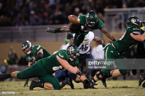 Cal Poly Mustangs running back Chuby Dunu fumbles the ball as he tries to jump over a player during the game between the Northern Arizona Lumberjacks...