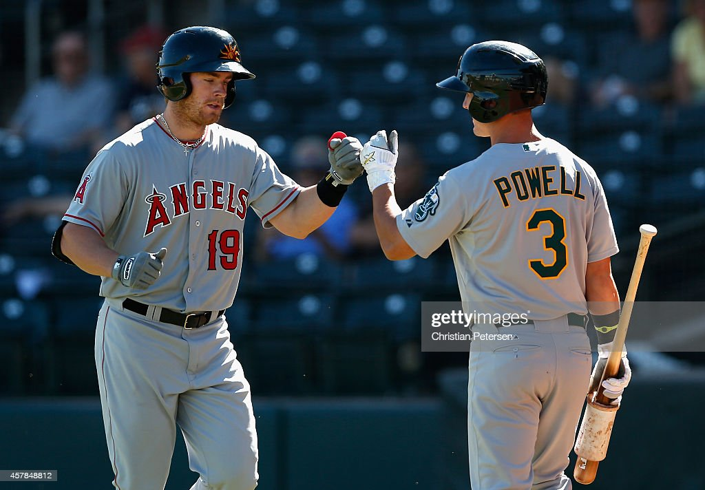 Cal Towey #19 (Los Angeles Angels of Anaheim) of the Mesa Solar Sox high-fives Boog Powell #3 (Oakland Athletics) after scoring against the Surprise Saguaros during the Arizona Fall League game at Surprise Stadium on October 21, 2014 in Surprise, Arizona.