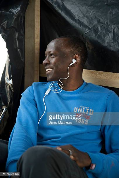 Calais August 2015 The Jungle camp of migrants most of whom are trying to get to England A seventeen year old Sudanese boy listens to music on his...