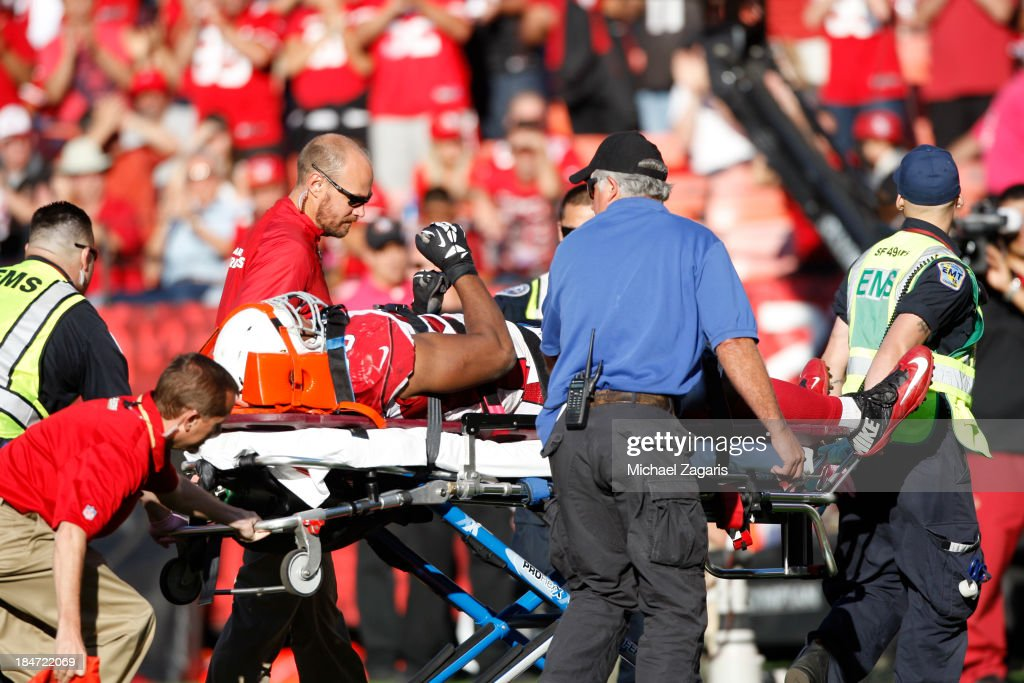 Calais Campbell of the Arizona Cardinals raises his arm to show he is OK as he is being taken away on a stretcher during the game against the San Francisco 49ers at Candlestick Park on October 13, 2013 in San Francisco, California. The 49ers defeated the Cardinals 32-20.