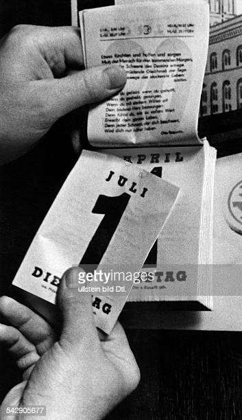 A calander sheet showing the date 1st of July is being held in front of the calender sheet of the 1st of april 1941 Photographer Herbert Hoffmann...