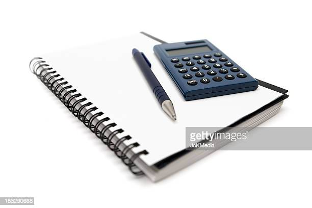 Calculator and pen on a wire bound notebook, on white