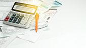 A calculator , ball pen and household bills , adding light