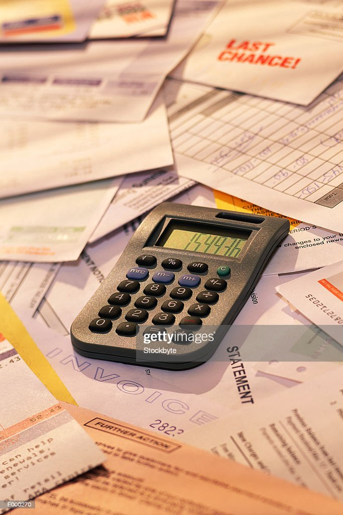 Calculator on pile of invoices : Stock Photo