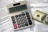 tax reform text on calculator screen with hundred dollar bill on 1040 income tax form