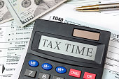 Calculator with text 'Tax Time' on tax forms and money. Business concept.