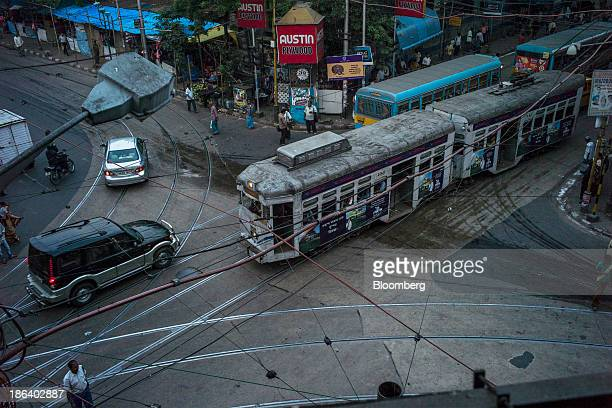 A Calcutta Tramways Company Ltd tram passes buses and cars at an intersection in Kolkata West Bengal India on Wednesday Oct 30 2013 Asia's...