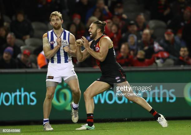 Cale Hooker of the Bombers pushes Daniel Nielson of the Kangaroos as he celebrates after scoring a goal during the round 18 AFL match between the...