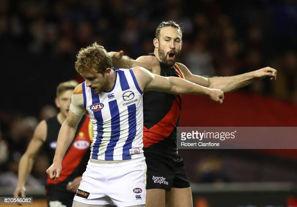 Cale Hooker of the Bombers taps the head of Daniel Nielson of the Kangaroos as he celebrates after scoring a goal during the round 18 AFL match...
