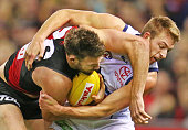 Cale Hooker of the Essendon Bombers is tackled by Daniel Talia of the Crows during the round 20 AFL match between the Essendon Bombers and the...
