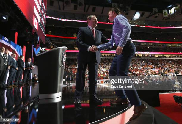 Cale Makar fourth overall pick of the Colorado Avalanche shakes hands with NHL Commissioner Gary Bettman during Round One of the 2017 NHL Draft at...