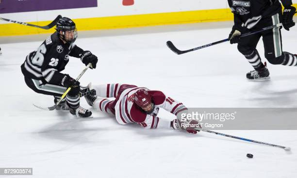 Cale Makar of the Massachusetts Minutemen is tripped by Brian Pinho the Providence College Friars during NCAA hockey at the Mullins Center on...