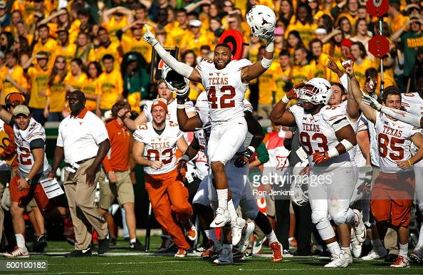 Caleb Bluiett of the Texas Longhorns celebrates with teammates after the Longhorns defeated the Baylor Bears 2317 at McLane Stadium on December 5...