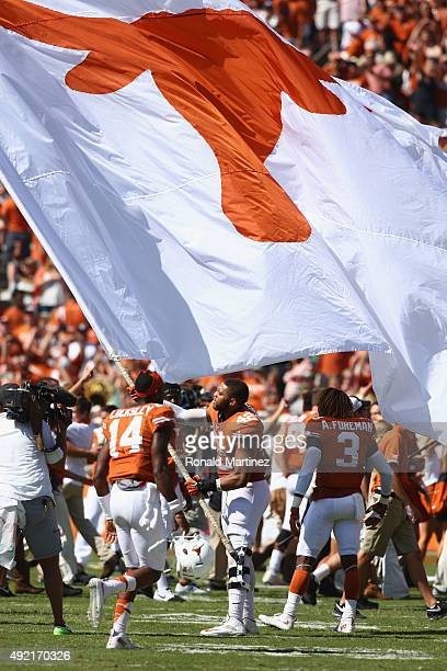 Caleb Bluiett of the Texas Longhorns waves a flag aftera 2417 win against the Oklahoma Sooners during the 2015 ATT Red River Showdown at Cotton Bowl...