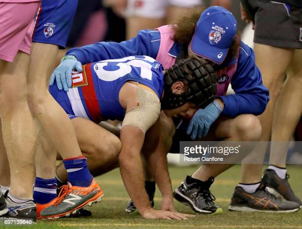 Caleb Daniel of the Bulldogs comes off the ground with an injury during the round 13 AFL match between the Western Bulldogs and the Melbourne Demons...